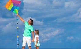 愉快的父亲和小女孩飞行风筝一起 免版税库存照片