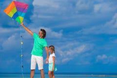 愉快的父亲和逗人喜爱的小的女儿飞行风筝 库存照片