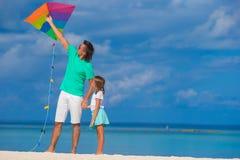 愉快的父亲和逗人喜爱的小的女儿飞行风筝 免版税库存照片