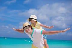愉快的父亲和他可爱的矮小的女儿获得乐趣在热带海滩 免版税图库摄影