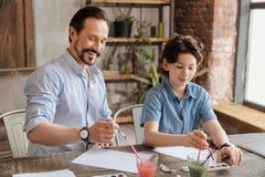 愉快的父亲和他的儿子集中于绘画 库存图片