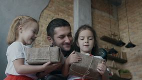 愉快的父亲在他们的手上的亲吻他的双女儿拿着圣诞节礼物 小女孩-浅黑肤色的男人和金发碧眼的女人是 股票录像