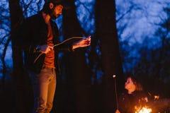 愉快的父亲在火前面在他的手上的站立在森林里拿着小树枝在晚上 库存图片