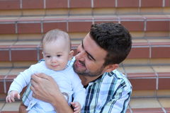 愉快的父亲在他的手上的拿着男婴 免版税库存照片
