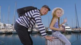 愉快的父亲女儿坐手提箱在海巡航一起去在海港 股票录像