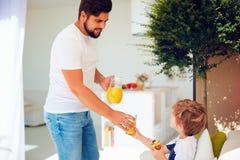 愉快的父亲对待儿子与新鲜的汁液和鲜美点心在夏天露台庭院 免版税库存图片