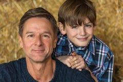 愉快的父亲微笑在干草捆的儿子人和男孩 免版税图库摄影