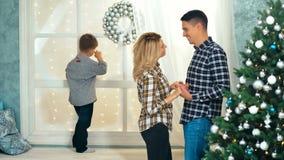 愉快的父亲母亲谈话在圣诞树附近,当他们的等待窗台的时儿子圣诞老人 影视素材