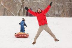 愉快的父亲照片和儿子在冬天走与管材 免版税库存图片