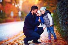 愉快的父亲画象有儿子的沿秋天街道的步行的 免版税库存照片