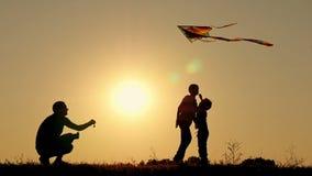 愉快的父亲跑蛇入空气 两个孩子是使用,嬉戏和跳过风筝 家庭团结 影视素材