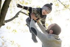 愉快的父亲画象有儿子的在秋天公园 免版税图库摄影