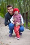 愉快的父亲画象有女儿的在公园 免版税库存照片