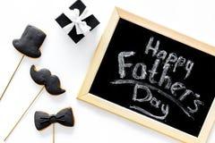 愉快的父亲` s天卡片 半正式礼服,髭和帽子曲奇饼和礼物 白色书桌背景顶视图 免版税图库摄影