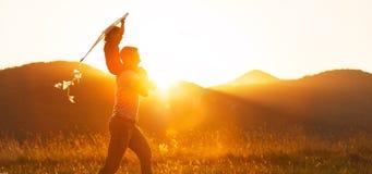 愉快的父亲` s天!儿童女孩和爸爸有一只风筝的在自然 库存照片
