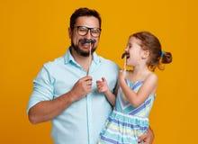 愉快的父亲` s天!滑稽的爸爸和女儿有髭唬弄的 库存照片
