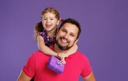 愉快的父亲` s天!逗人喜爱的拥抱在紫罗兰后面的爸爸和女儿 免版税库存图片