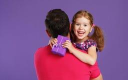 愉快的父亲` s天!逗人喜爱的拥抱在紫罗兰后面的爸爸和女儿 库存图片