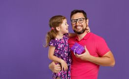 愉快的父亲` s天!逗人喜爱的拥抱在紫罗兰后面的爸爸和女儿 库存照片
