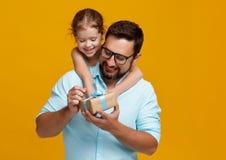 愉快的父亲` s天!逗人喜爱的拥抱在黄色后面的爸爸和女儿 免版税库存照片