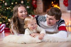 愉快的父母和孩子在家获得一个乐趣在圣诞树附近 一起庆祝新年的父亲、母亲和儿子 免版税库存图片