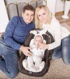 愉快的父母和岁孩子一套兔宝宝衣服的在客厅 库存照片