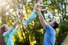 愉快的父母在公园附寄ittle女孩 免版税图库摄影