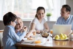 愉快的父母手表激发使用在kitche的智能手机的孩子 免版税库存图片