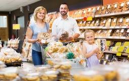 愉快的父母用女儿买的面包 免版税库存照片