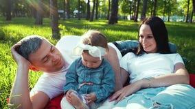 愉快的父母看使用与她的在绿草的鞋子的女婴在公园 股票录像