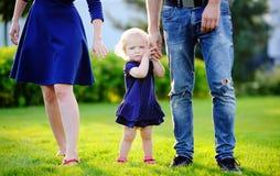 愉快的父母身分:有他们的甜小孩女孩的年轻父母 免版税库存图片