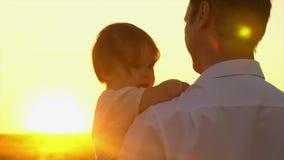 愉快的爸爸在他的胳膊拿着一点女儿在美丽的太阳的光芒的公园 走与一个小孩子的爸爸 股票录像