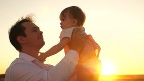 愉快的爸爸在公园亲吻一点女儿 愉快的童年的概念 有小儿童游戏的父亲在a光芒  影视素材