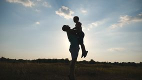 愉快的爸爸在天空中的投掷他的小男孩在自然 使用在草甸的父亲和儿子剪影在 股票视频
