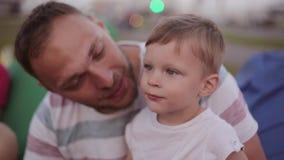 愉快的爸爸在面颊亲吻他逗人喜爱的儿子 花费时间的父亲和儿子在公园在夏天,男孩指向某事 股票录像