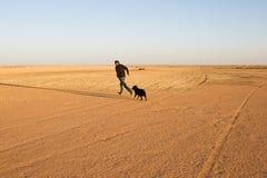 愉快的片刻:人奔跑和戏剧与他的狗在沙漠 库存照片