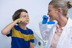 愉快的牙医和男孩掠过的牙对墙壁 免版税库存图片