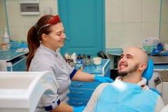 愉快的牙医和患者在牙齿办公室 免版税库存照片