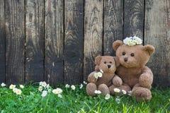 愉快的玩具熊-照顾和她的木背景的婴孩为 免版税库存照片
