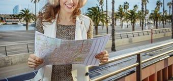 愉快的现代妇女在巴塞罗那,看地图的西班牙 库存图片