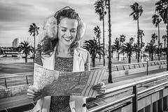 愉快的现代妇女在巴塞罗那,看地图的西班牙 免版税库存照片