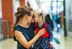 愉快的现代母亲和女儿在购物中心拥抱的万圣夜 库存图片