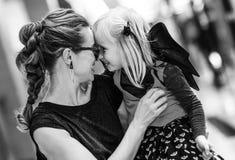 愉快的现代母亲和女儿在购物中心拥抱的万圣夜 免版税库存图片