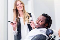 愉快的理发师和微笑的顾客沙龙的 免版税图库摄影