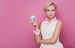 愉快的生日 拿着与五颜六色的蜡烛的美丽的少妇小蛋糕 免版税库存照片