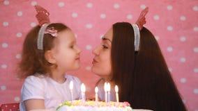 愉快的生日 母亲和孩子做一个愿望并且吹灭在蛋糕的蜡烛在党 妈妈祝贺,容忍和 影视素材