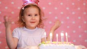 愉快的生日 逗人喜爱的孩子做一个愿望并且吹灭在蛋糕的蜡烛在党 滑稽的女孩一点 桃红色背景 股票录像