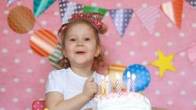 愉快的生日 逗人喜爱的孩子做一个愿望并且吹灭在蛋糕的蜡烛在党 滑稽的女孩一点 桃红色背景 股票视频