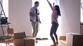 愉快的生活在修理以后的新房里,有女孩快乐舞蹈的快乐的男朋友在搬入公寓期间与 股票录像