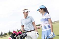愉快的男人和妇女交谈在高尔夫球场反对清楚的天空 库存图片